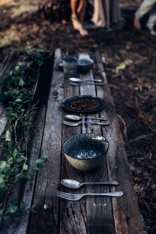 Table setting placed on wooden bench in forest