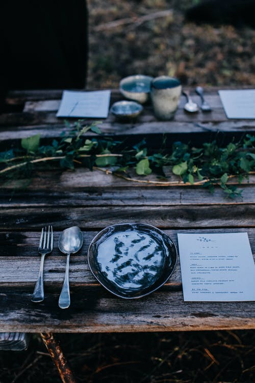 Table setting on shabby wooden table in woodland