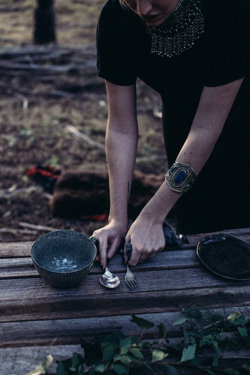 Crop female in black dress putting cutlery and dinnerware on shabby wooden table in woodland for picnic