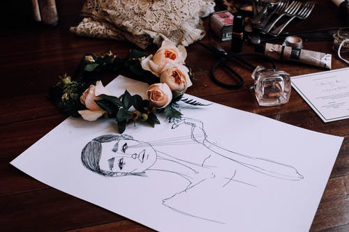 Creative drawing placed on vanity table with scattered cosmetics