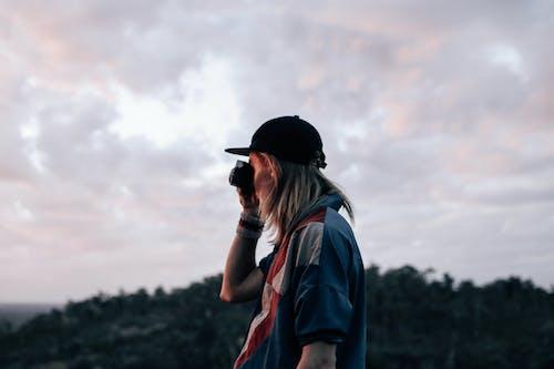 Unrecognizable person taking photo in evening nature
