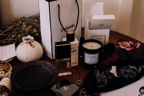 Composition of various makeup products aroma candles and black lace bra placed on wooden vanity table in light room