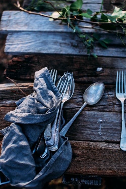 Cutlery on crumpled cloth on wooden table