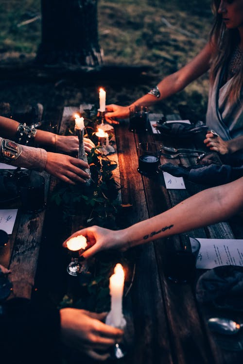 Crop fortune tellers with burning candles at table outdoors