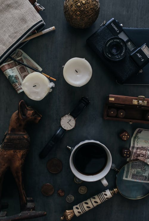 Top view of retro photo camera near wristwatch and dog statuette with hot drink on table