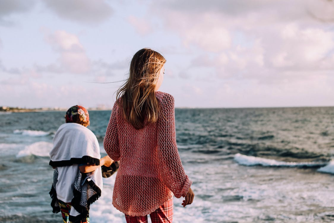 Anonymous siblings contemplating wavy sea under cloudy sky