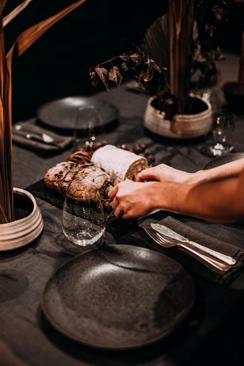 Crop anonymous person putting baked treat and sweet roll on table with glassware and cutlery during festive event