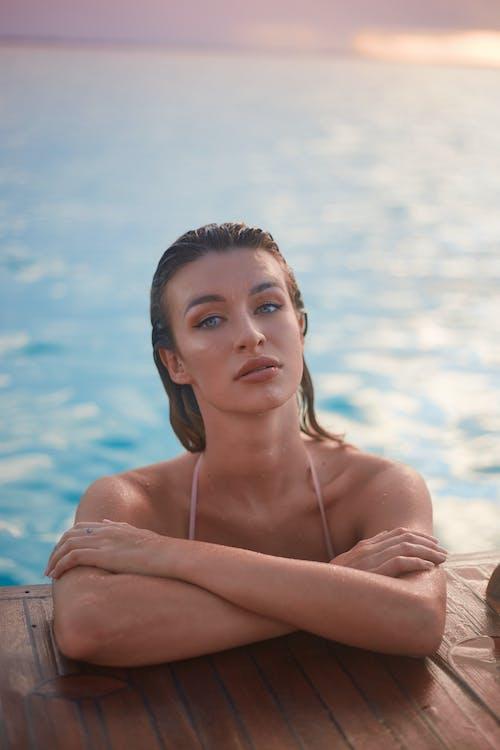 Sensual young woman resting in sea at sundown