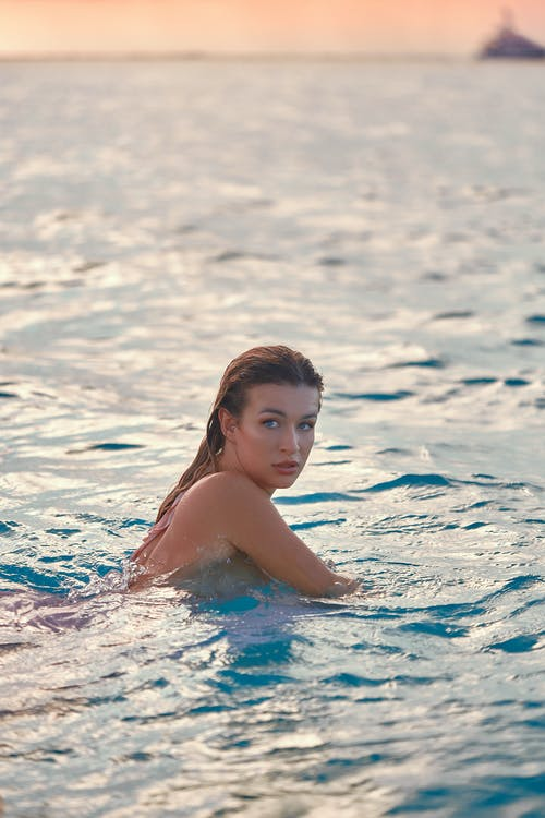 Graceful young female tourist swimming in ocean at sundown