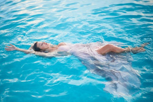 Feminine young woman floating in water