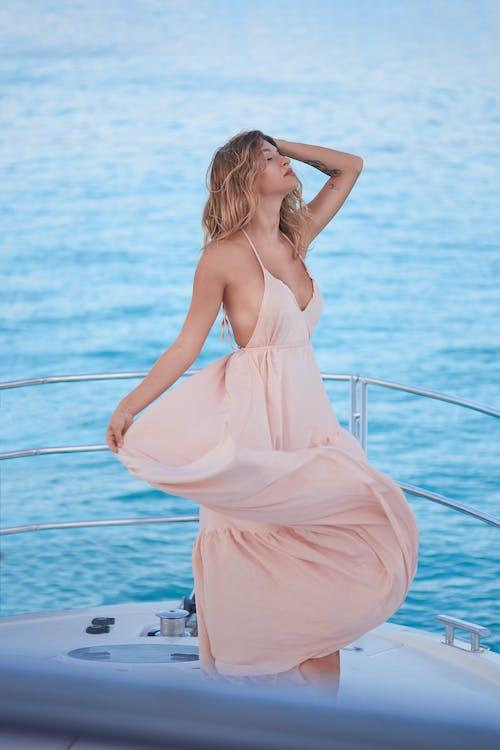 Sensual young woman enjoying summer vacation on yacht