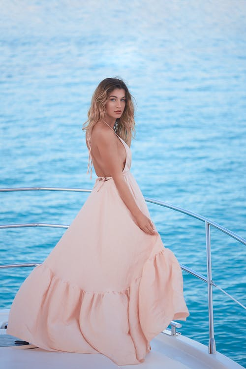 Gorgeous young female resting on yacht sailing in sea