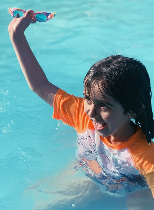 Happy child with goggles in swimming pool