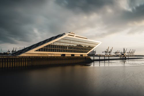 Brown Wooden House on Water Under Gray Clouds