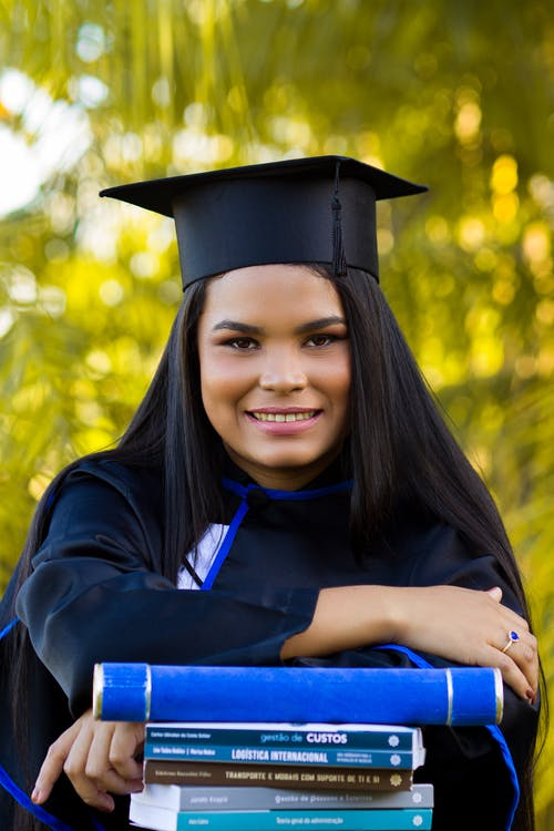 Glad young ethnic woman in graduation cap with textbooks smiling and looking at camera on blurred background of greenery