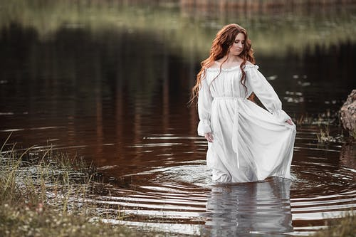 Thoughtful woman standing in lake water