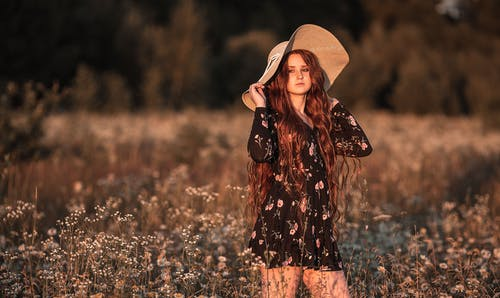 Romantic female in casual dress and straw hat standing in meadow and looking away