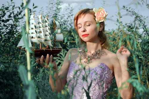 Young dreamy woman with closed eyes wearing elegant party outfit standing with small sail ship model in green garden