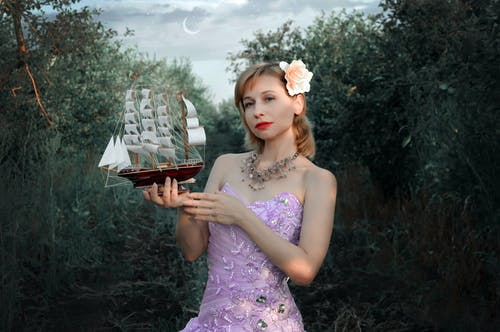 Young dreamy woman in elegant dress and with flower in hair holding small ship model looking away in evening garden