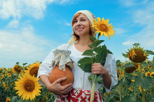 Happy woman in countryside with clay jug and sunflower