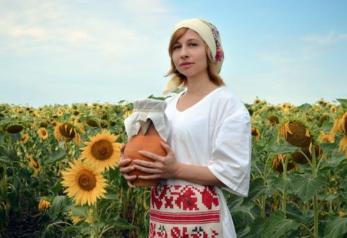Young woman in country outfit with clay jug in sunflower field in sunny summer day