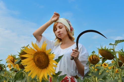 Tired woman with scythe working in field