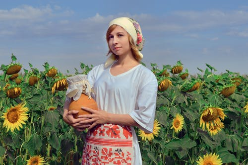 Wistful woman standing among blooming sunflowers