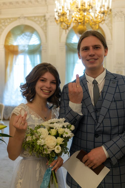 Happy newlywed couple showing wedding rings on fingers