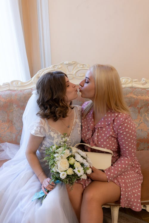 Stylish bride kissing bridesmaid on couch on wedding day