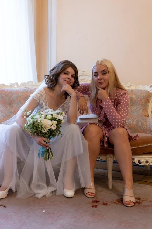 Trendy bride with flowers near bridesmaid on sofa