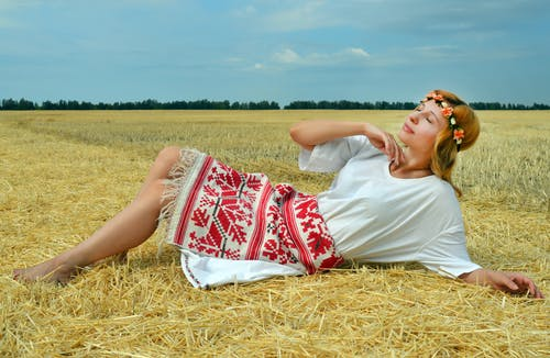 Young glad female in traditional clothes lying on straw on meadow and enjoying sunny day