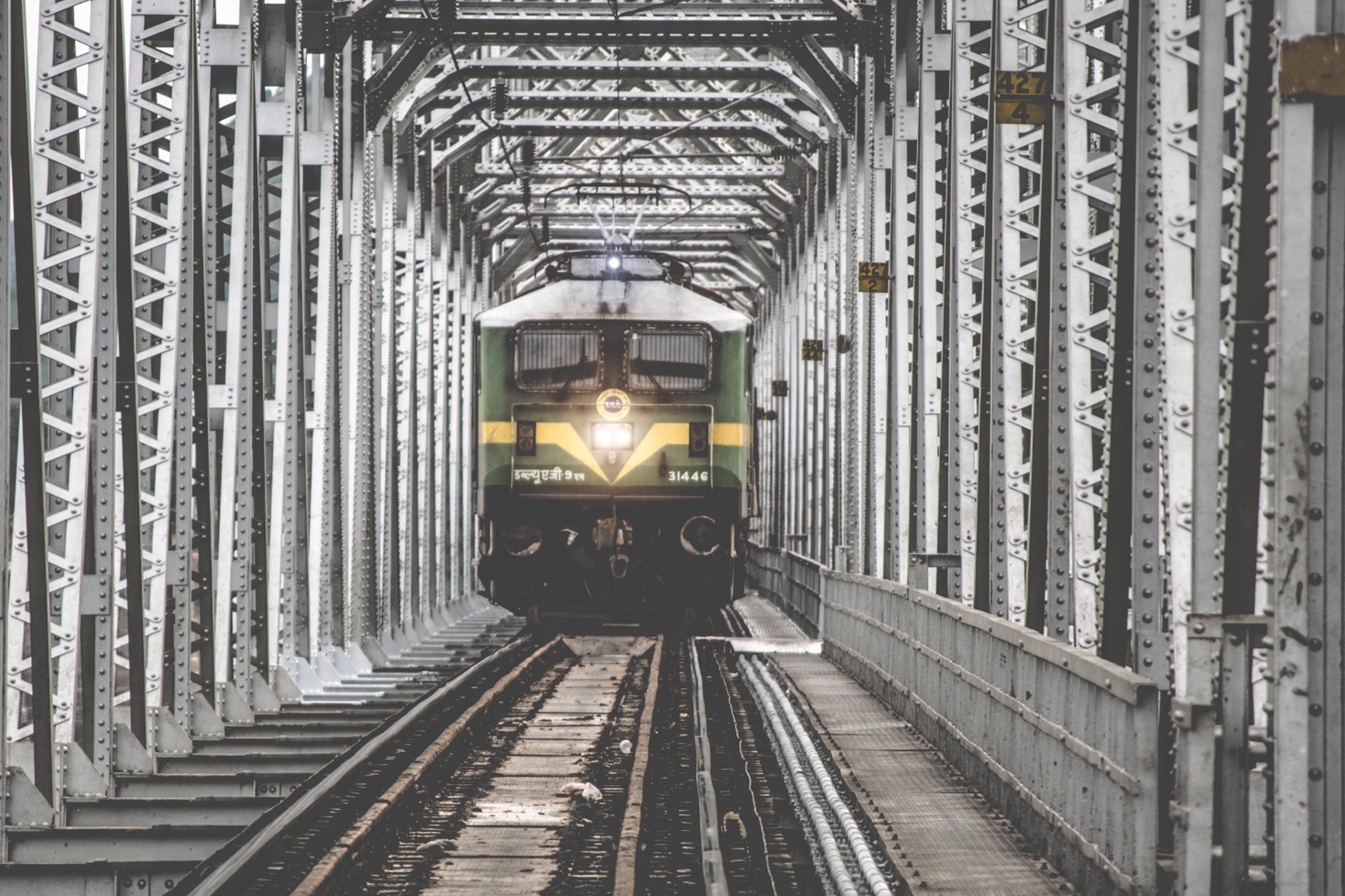 Green Train Coming Forward on White Metal Frame