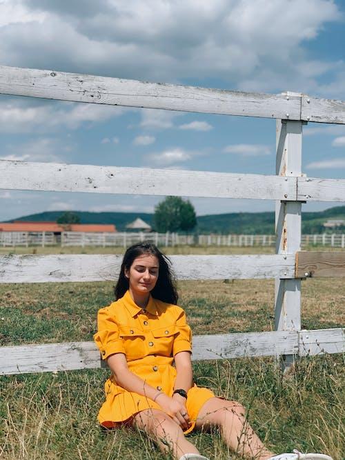 Stylish young female sitting on grassy meadow near paddock on farm