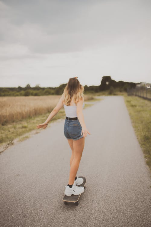 Woman in White Tank Top and Blue Denim Shorts Running on Road