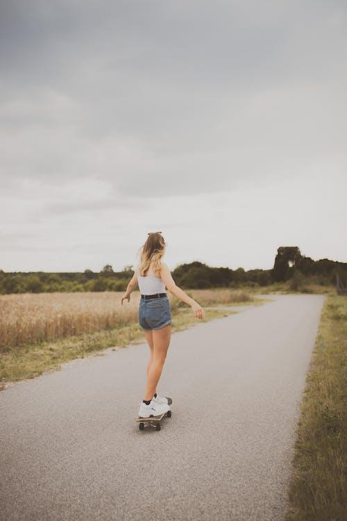 Woman in Blue Denim Shorts Walking on Road