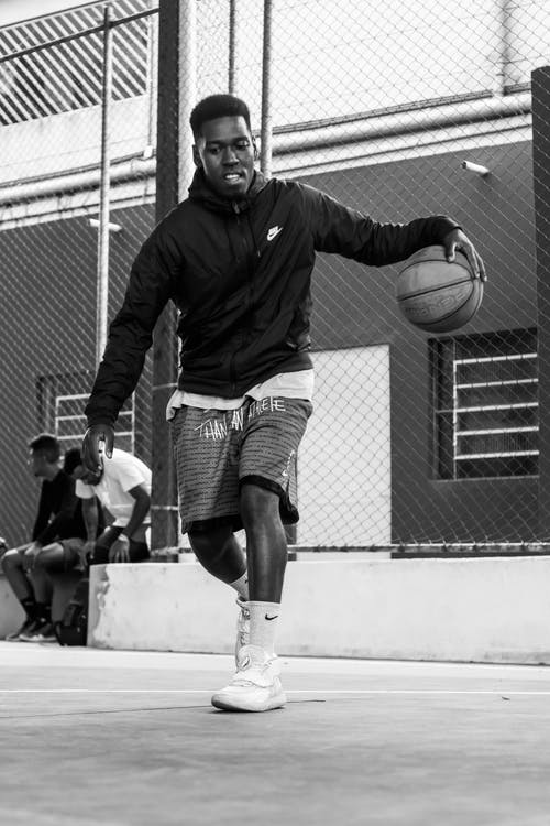 Young active black man playing basketball on street