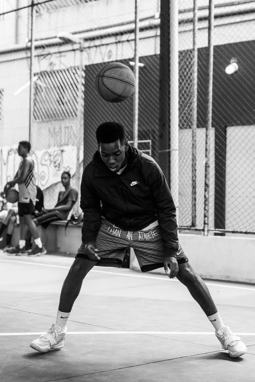 Concentrated young black guy playing streetball during outdoor training
