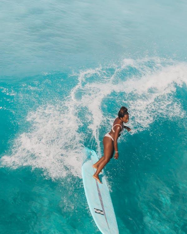 Woman in Black Bikini Sitting on White Surfboard on Blue Sea