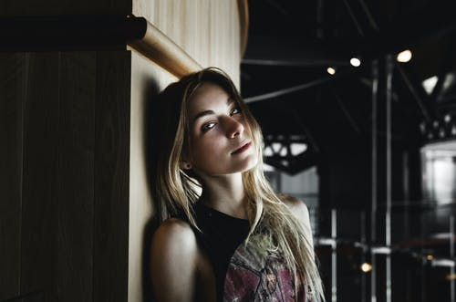 Dreamy young blondie leaning on wall and relaxing