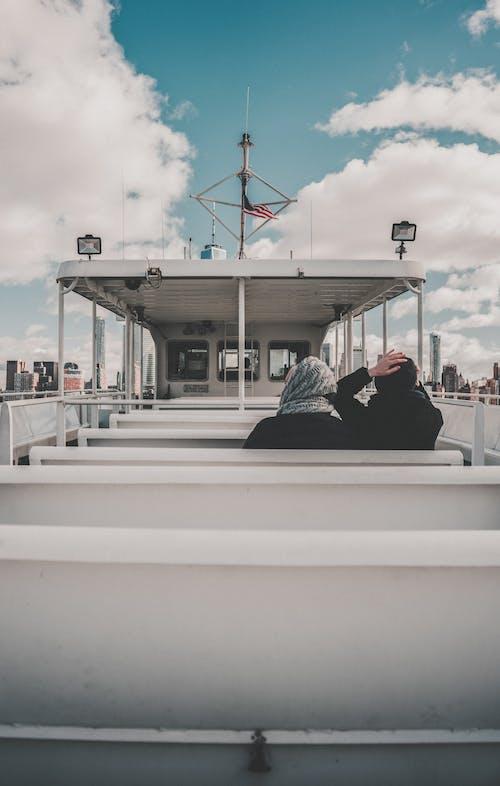 Man in Black Jacket Sitting on White Boat