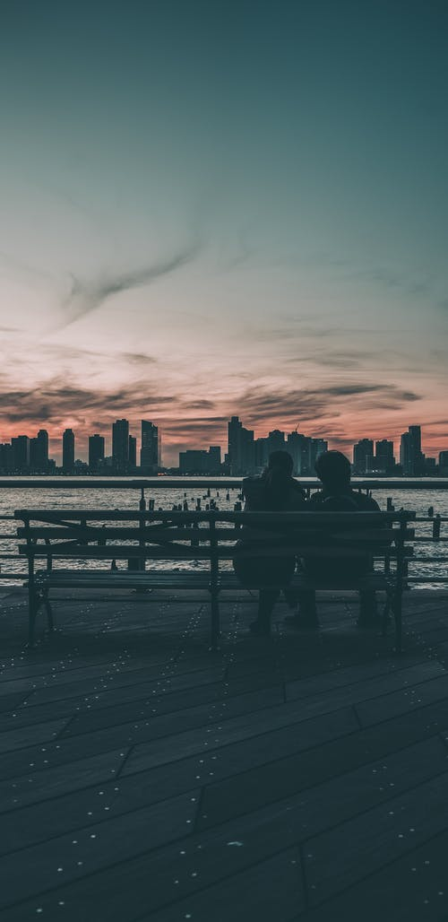 Silhouette of People Sitting on Bench Near Body of Water during Sunset