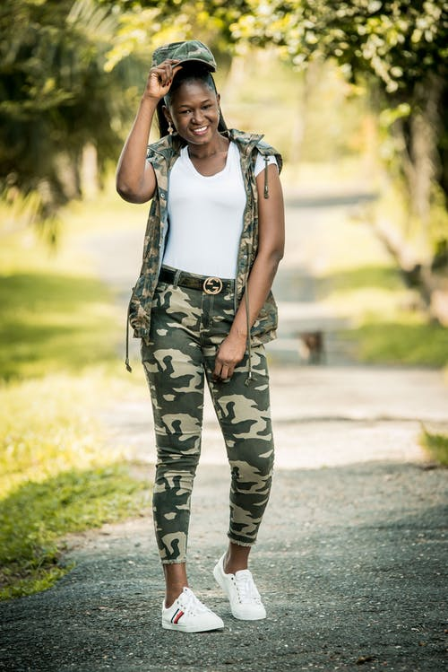 Woman in White Tank Top and Green and Black Camouflage Pants Standing on Road