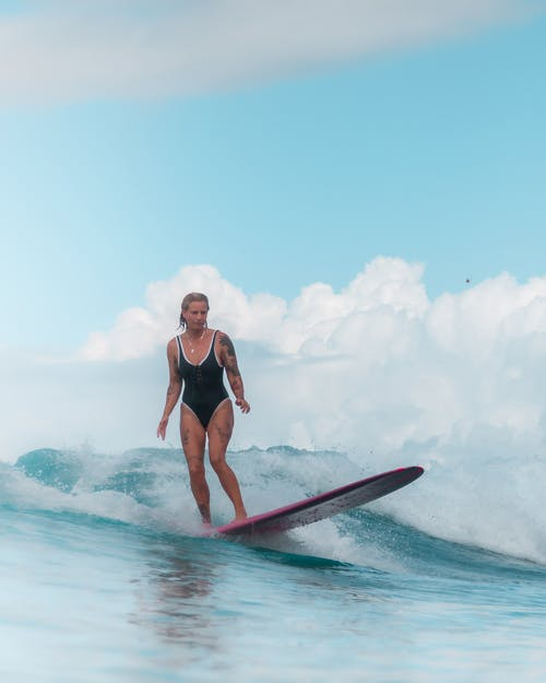 Woman in Black Swimsuit Riding on Surfboard