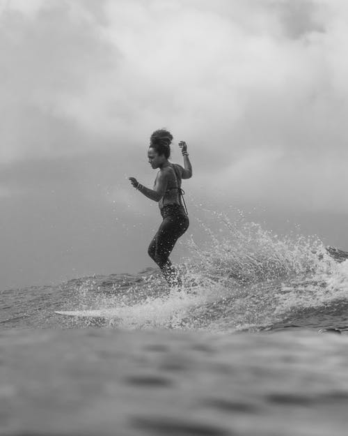 Grayscale Photo of Woman in Black Tank Top and Black Shorts Surfing on Water