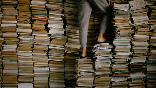 Person Standing on Stacks of Books