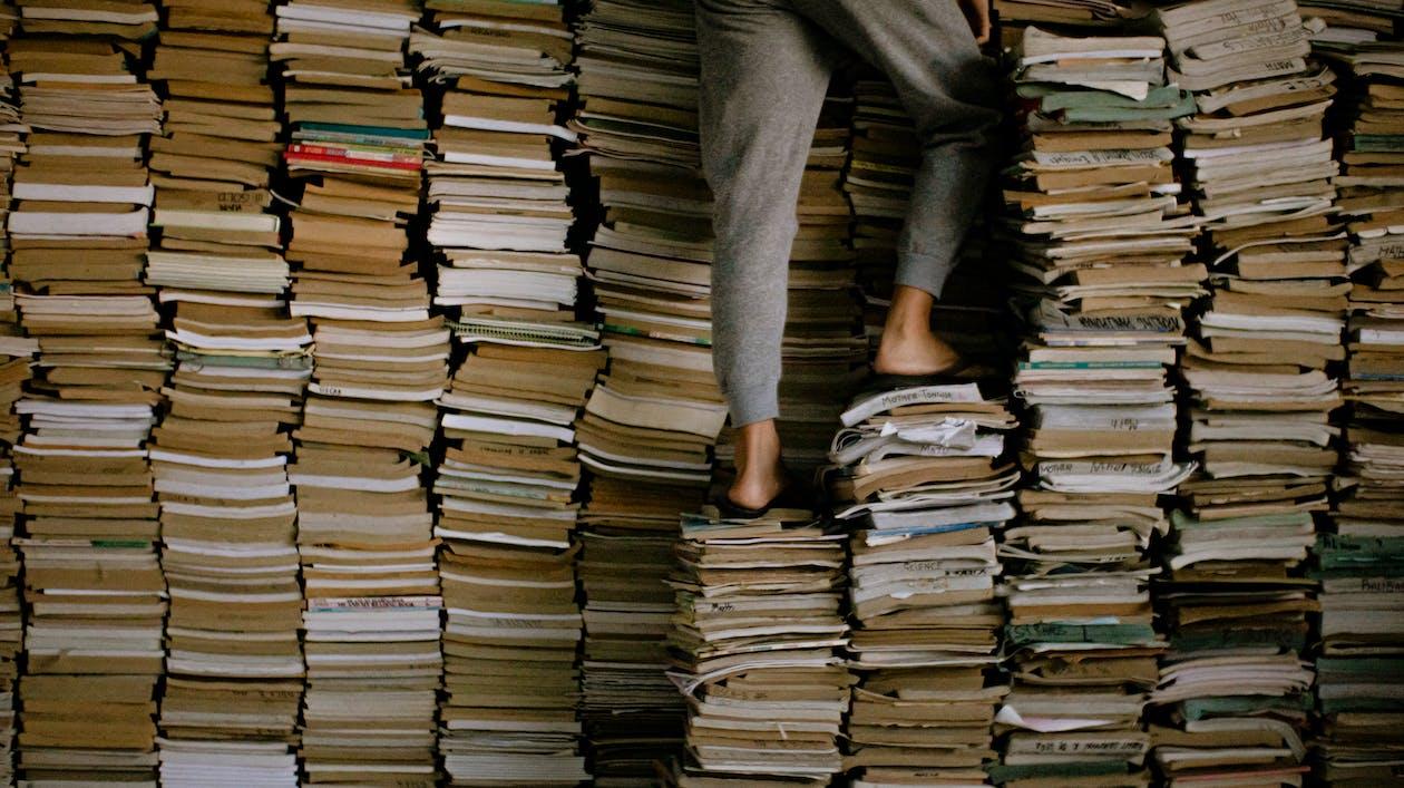 Человек, стоящий на стопках книг