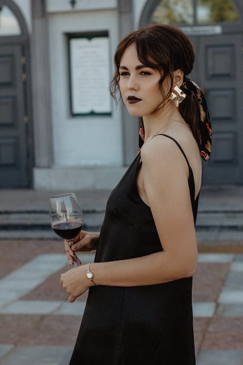 Trendy young lady enjoying wine during event in luxury outdoor restaurant