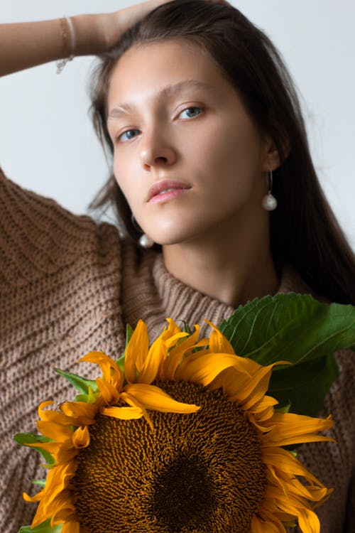 Calm young woman with sunflower looking at camera