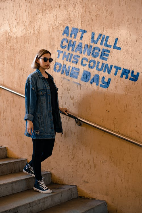Trendy woman walking down stairs near wall with title