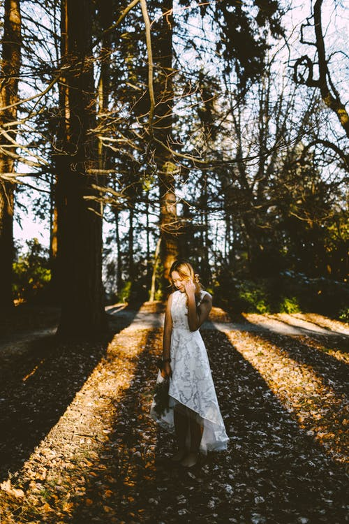 Woman in White Dress Standing on Pathway Surrounded by Trees